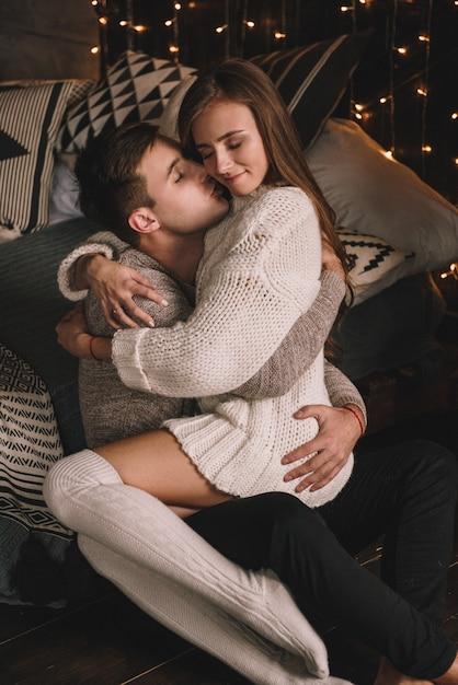 casal-na-cama-no-quarto-interior-escuro-abracos-e-beijos-estar-apaixonado-camisola-branca-e-meias-altas-encontro-romantico-a-data-amantes-ternura_102037-1119.jpg
