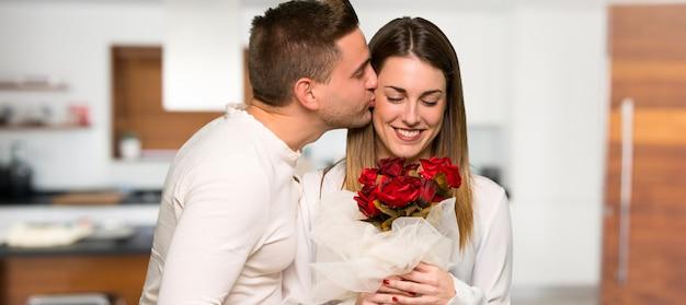 Casal no dia dos namorados com flores em uma casa Foto Premium