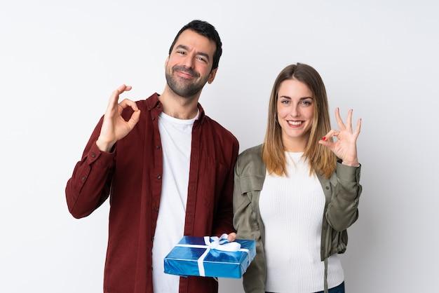 Casal no dia dos namorados, segurando um presente na parede isolada, mostrando um sinal de ok com os dedos Foto Premium
