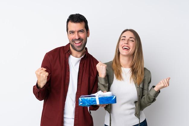 Casal no dia dos namorados, segurando um presente sobre parede isolada, comemorando uma vitória na posição de vencedor Foto Premium
