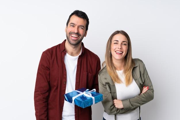 Casal no dia dos namorados, segurando um presente sobre parede isolada, mantendo os braços cruzados enquanto sorrindo Foto Premium