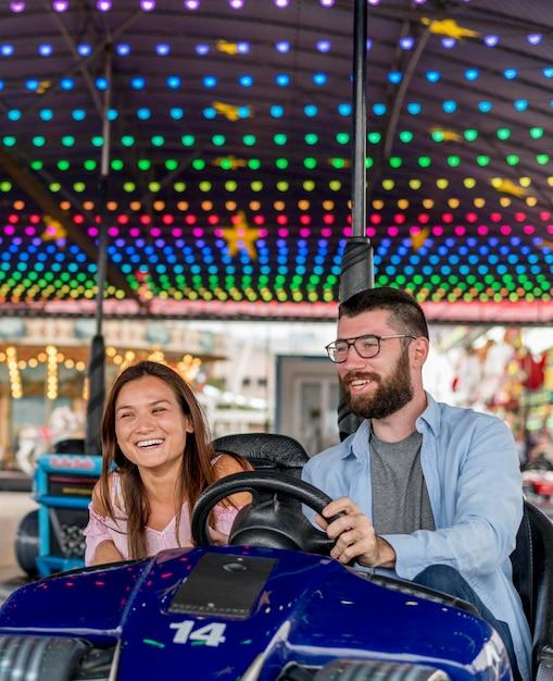 Casal no parque de diversões se divertindo com carrinhos de choque Foto Premium