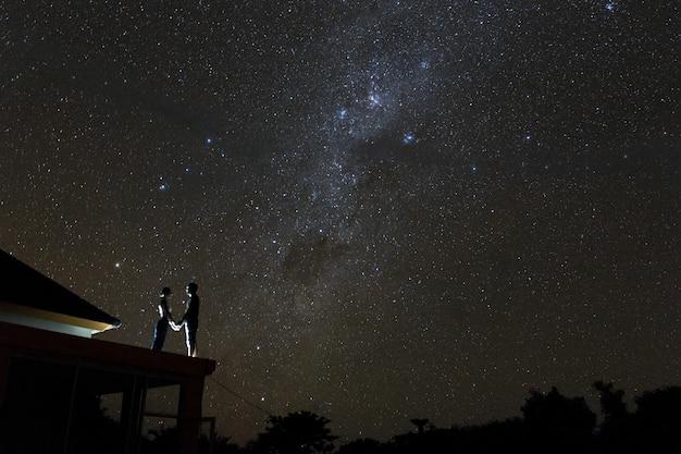 Casal no telhado assistindo mliky maneira e estrelas no céu noturno Foto Premium