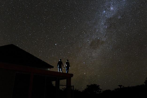 Casal no telhado assistindo mliky way e estrelas no céu noturno na ilha de bali Foto Premium