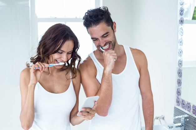 Casal olhando no celular enquanto escovar os dentes Foto Premium
