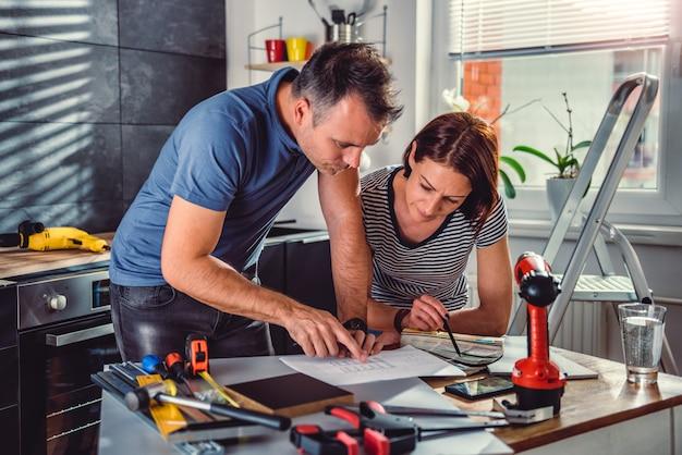 Casal olhando plantas durante a renovação da cozinha Foto Premium