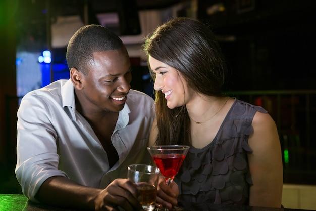 Casal olhando um ao outro e sorrindo enquanto toma bebidas no bar Foto Premium