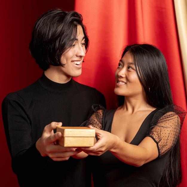 Casal olhando um ao outro segurando presente para o ano novo chinês Foto gratuita