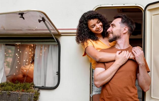 Casal parado em frente a uma van e olhando um para o outro Foto gratuita