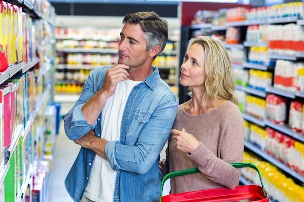 Casal pensativo, escolhendo um produto no supermercado Foto Premium