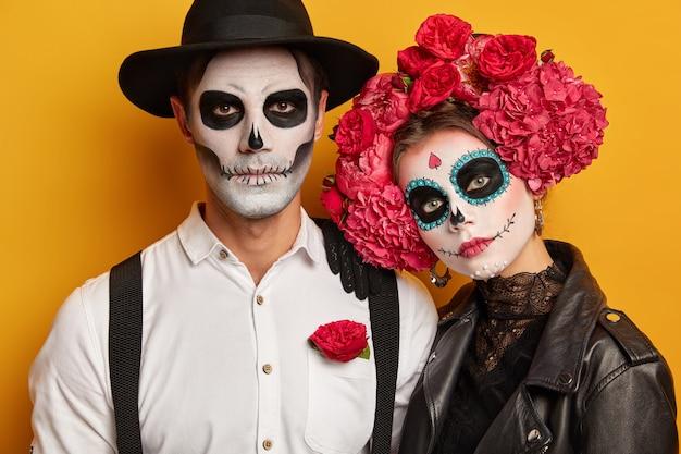 Casal pintou rostos, participa de caminhada de zumbis, comemora mortos durante o dia da morte no méxico e usa maquiagem de festa de halloween Foto gratuita