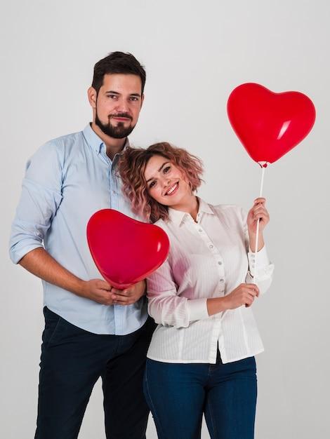 Casal posando com balões para dia dos namorados Foto gratuita