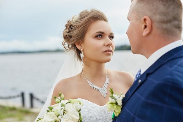 Casal, qua, abraçar, e, beijo, próximo, casas, perto, água Foto Premium