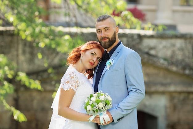 Casal recém casado amoroso hipster em vestido de noiva e terno no parque Foto Premium