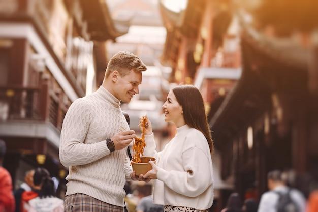 Casal recém-casado comendo macarrão com pauzinhos em xangai, fora de um mercado de alimentos Foto gratuita
