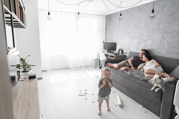Casal relaxando no sofá com o cão e seu filho brincando com brinquedos em casa Foto gratuita