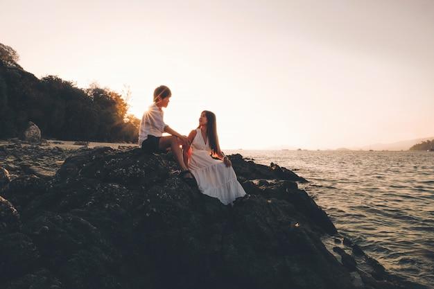 Casal relaxante belo pôr do sol na praia de koh lipe tailândia, férias de verão Foto Premium