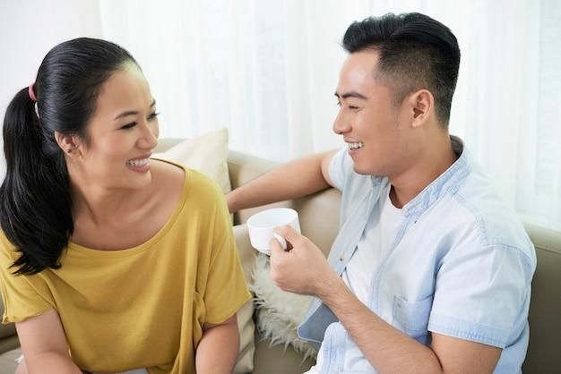 Casal rindo com café Foto gratuita