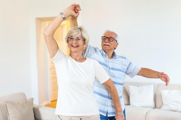 Casal romântico aposentado idoso ativo e alegre dançando Foto Premium