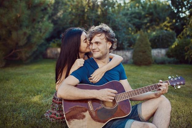 Casal romântico sentado na grama no jardim Foto gratuita