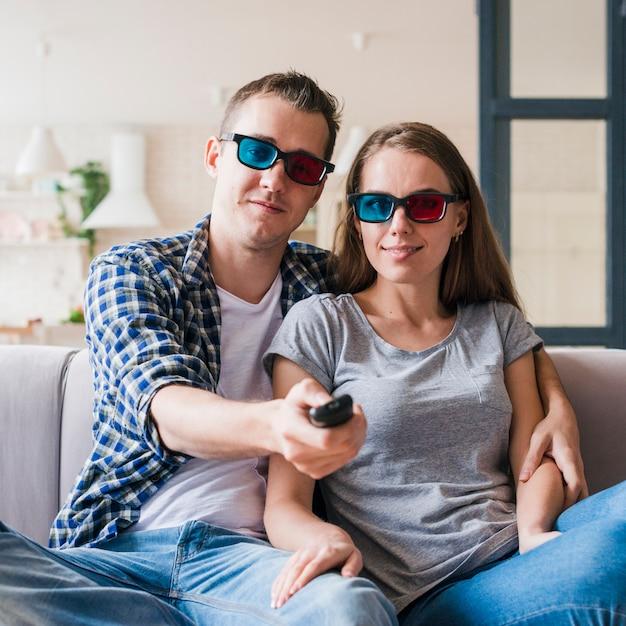 Casal satisfeito sentado no sofá e desfrutando de filme Foto gratuita