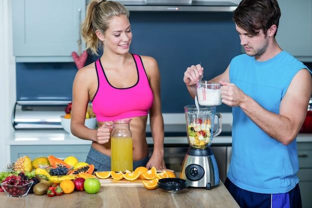 Casal saudável preparando um smoothie na cozinha Foto Premium