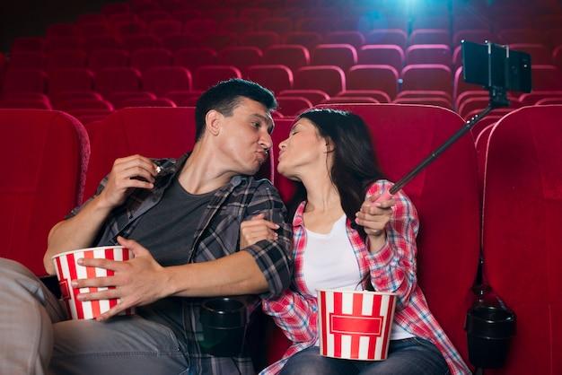 Casal se beijando e tomando selfie no cinema Foto gratuita