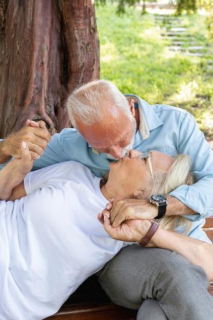 Casal se beijando em um banco no parque Foto gratuita