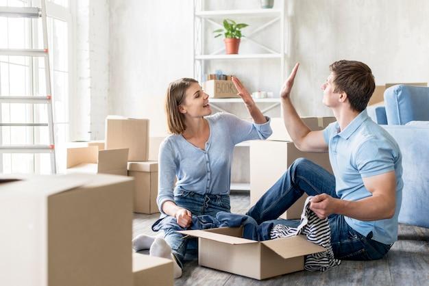 Casal se cumprimentando enquanto fazem as malas para mudar de casa Foto Premium