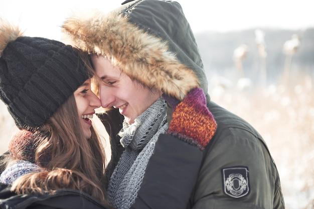 Casal se diverte e ri. beijo. casal jovem hippie, abraçando-se em winter park. história de amor de inverno, um lindo casal jovem e elegante. moda inverno com namorado e namorada Foto Premium