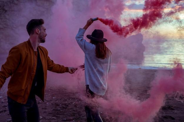 Casal se divertindo com bomba de fumaça rosa na costa do mar Foto gratuita