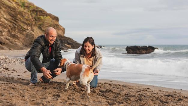 Casal se divertindo com cachorro Foto gratuita