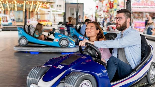 Casal se divertindo com carrinhos de choque no parque de diversões Foto Premium
