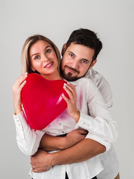 Casal segurando balão de coração e posando Foto gratuita
