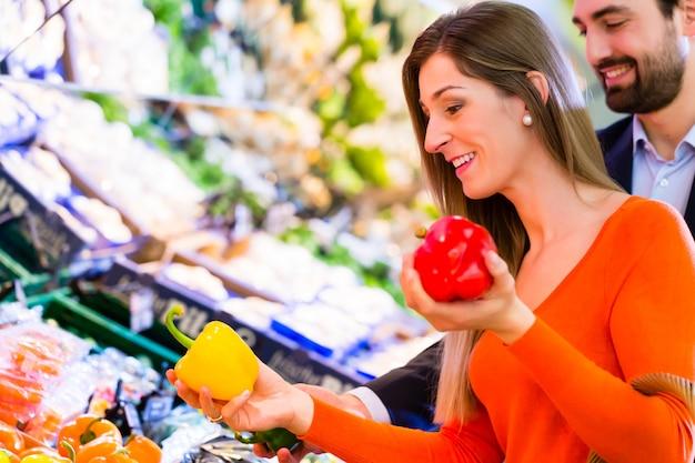 Casal selecionando legumes no hipermercado Foto Premium