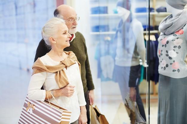 Casal sênior à procura de roupas novas, tempo de compras Foto gratuita