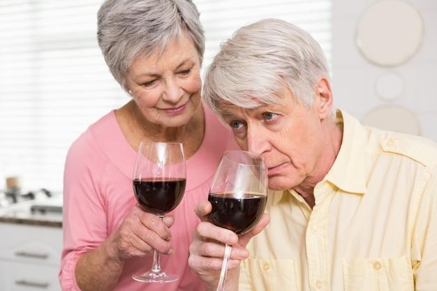 Casal sênior bebendo vinho tinto | Foto Premium