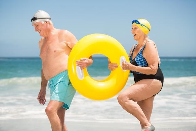 Casal sênior com anel de natação na praia Foto Premium