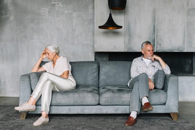 Casal sênior depois de uma discussão sentado em lados opostos do sofá Foto gratuita