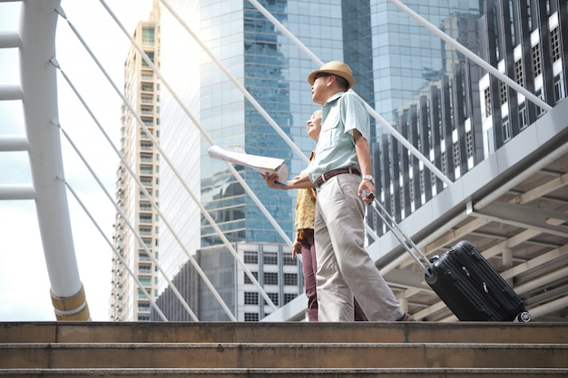 Casal sênior está andando, arrastando sua bagagem e segurando um mapa para navegar pelas ruas. Foto Premium