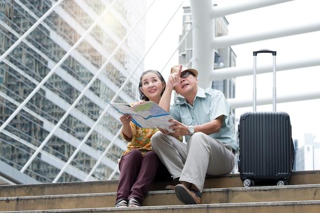 Casal sênior está sentado segurando o mapa para procurar destinos nas ruas. Foto Premium