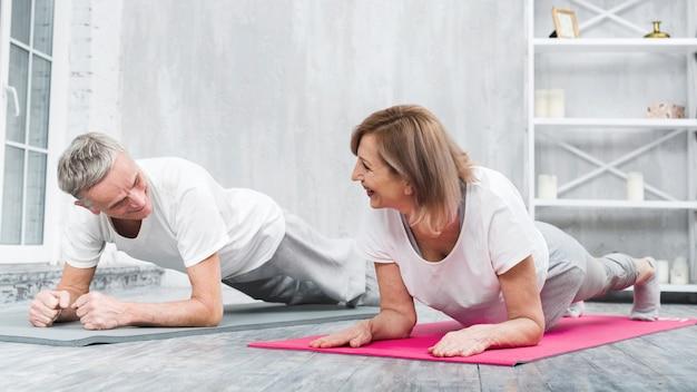 Casal sênior fazendo ioga juntos em casa Foto gratuita