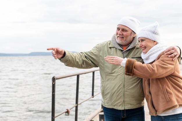 Casal sênior na beira-mar apontando juntos Foto gratuita