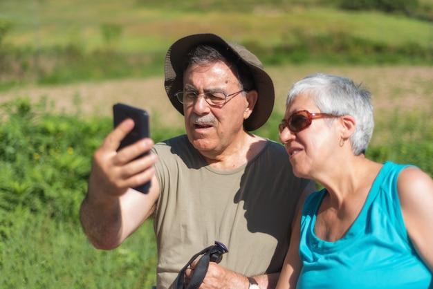 Casal sênior na caminhada tomando uma selfie Foto Premium