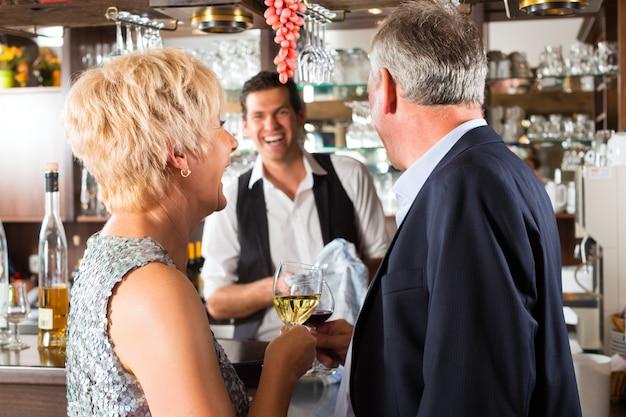 Casal sênior no bar com copo de vinho na mão Foto Premium