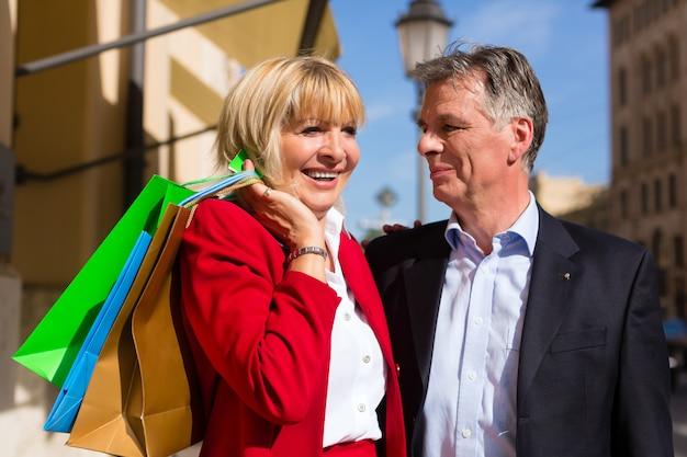 Casal sênior passeando pela cidade em compras de primavera Foto Premium