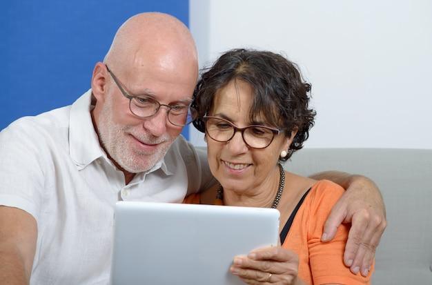 Casal sênior usando um tablet e sorrindo Foto Premium