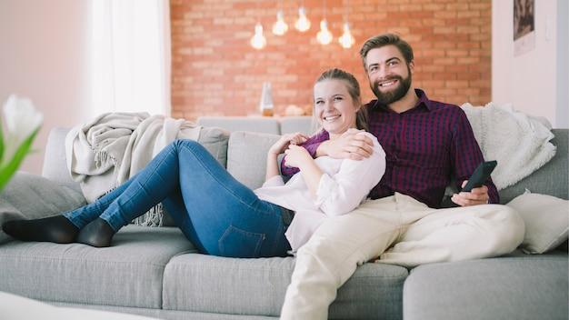 Casal sentado e assistindo televisão juntos Foto gratuita