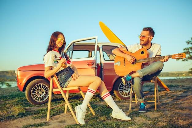 Casal sentado e descansando na praia tocando violão em um dia de verão perto do rio. homem e mulher caucasianos Foto gratuita