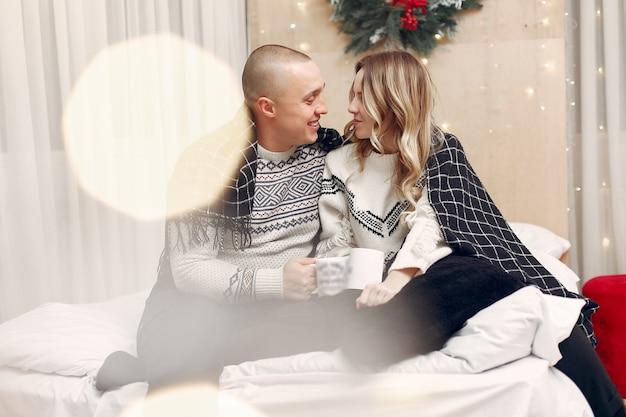 Casal sentado em uma cama tomando café Foto gratuita